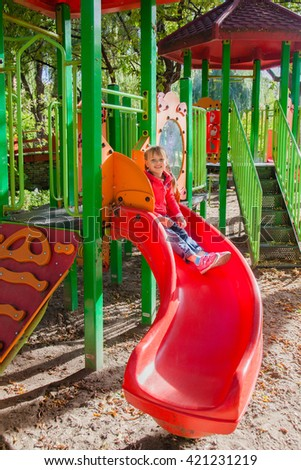 Preschool girl playing alone at children playground. Sliding from the top of slide. Summer time. - stock photo