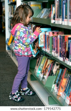 Preschool girl selecting book in library. (Portrait) - stock photo