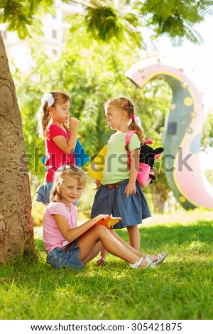 Preschool girl sits under a large tree at the park and reads a book - stock photo