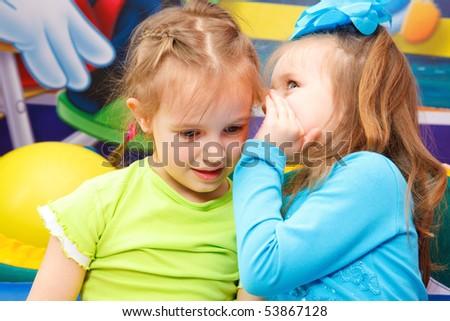 Preschool girl telling her friend some gossips - stock photo