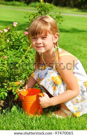 Preschool girl watering flowers in garden - stock photo