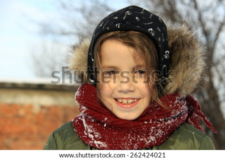 Preschool girl with auburn hair and brown eyes is playing with snow outside in a winter day. She is dressed with warm winter clothes. - stock photo