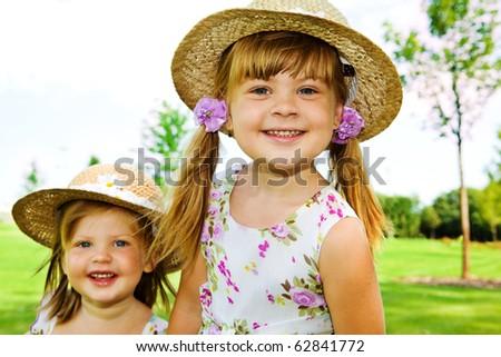 Preschool girls in straw hats - stock photo