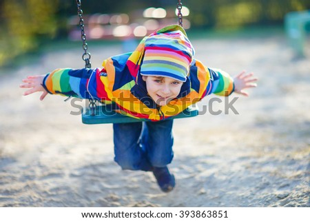 Preschool kid boy having fun with chain swing on outdoor playground. child swinging on warm sunny spring or autumn day. Active leisure with kids. Boy wearing colorful clothes - stock photo