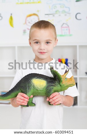 preschool kid playing with dinosaur - stock photo