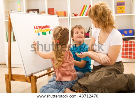 Preschool kids sitting on the floor doing math exercises with their mother - stock photo