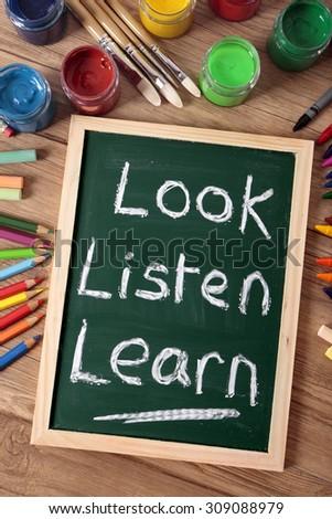 Preschool learning, Look, Listen, Learn writing on small blackboard, vertical - stock photo