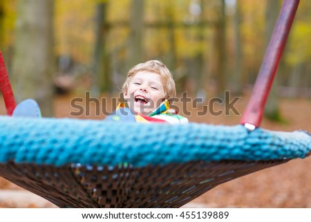 Preschool little kid boy having fun with chain swing on outdoor playground. child swinging on warm sunny autumn day. Active leisure with kids. Boy wearing colorful clothes - stock photo