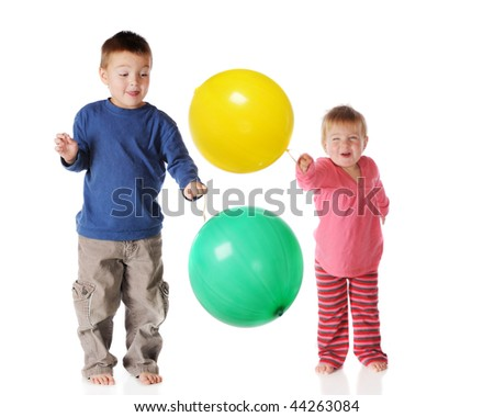 Preschool siblings happily playing together with punch-balls.  Isolated on white. - stock photo