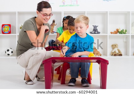 preschool students and female teacher in kindergarten - stock photo