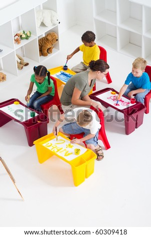 preschool students and teacher in classroom - stock photo