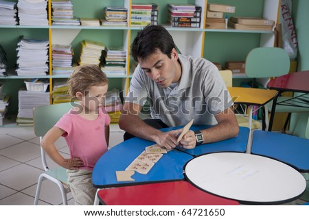 preschool teacher and child in the classroom counting - stock photo