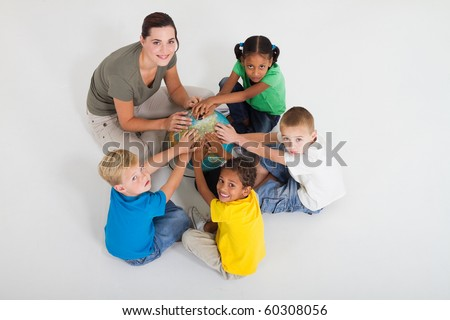 preschool teacher and students hands on a globe - stock photo