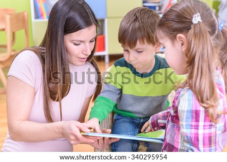 Preschool Teacher Reading A Book To Boy And Girl
