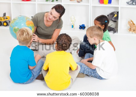 preschool teacher teaching kids about globe - stock photo