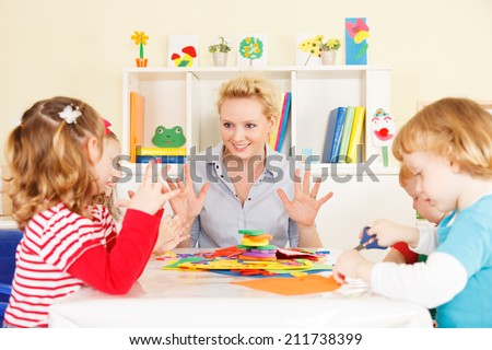 Preschool: Young smiling teacher discussing with group of children. Learning and having fun. Selective focus to teacher talking. - stock photo