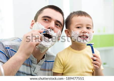 preschooler attempting to shave like his dad - stock photo