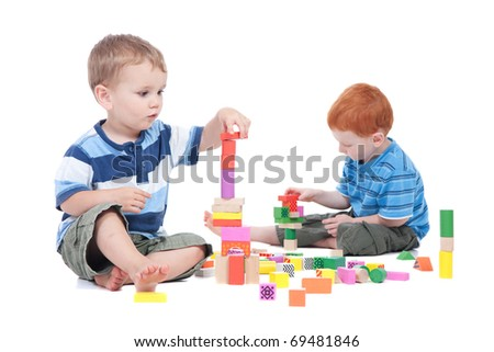 Preschooler boys playing with toy blocks.  Isolated on white. - stock photo