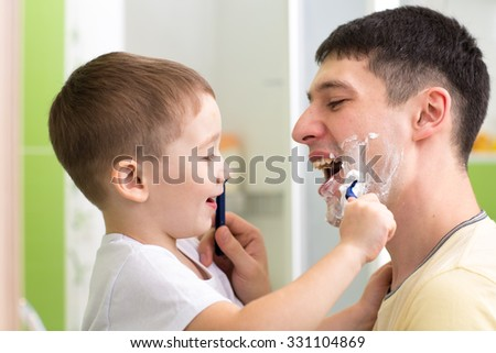 preschooler child attempting to shave his dad - stock photo