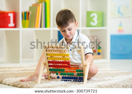preschooler child boy playing with counter toy - stock photo