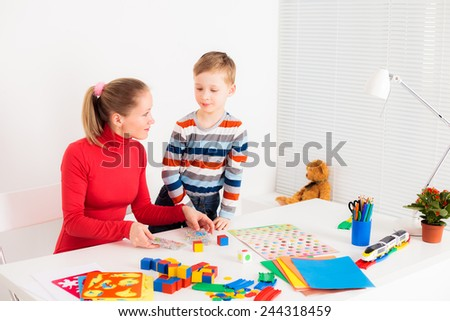 preschooler child playing in  board game with his mom - stock photo