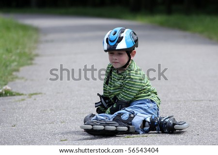 Preschooler falls over while rollerblading in the park - stock photo