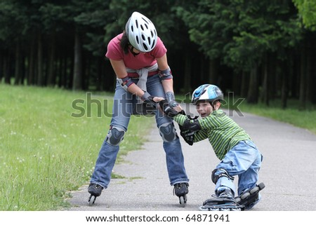 Preschooler falls over while rollerblading with mother in the park - stock photo