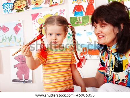 Preschooler girl and paintbrush with teacher draw paint in play room. - stock photo