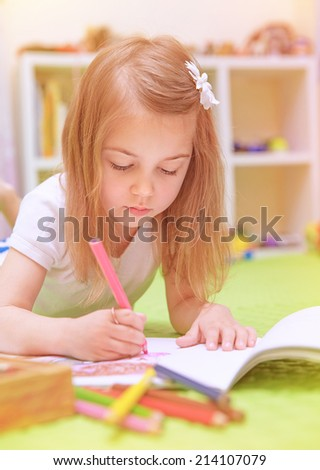 Preschooler girl painting with colourful pencil, lying down on the floor in daycare and enjoying art, elementary school, artistic childhood concept  - stock photo