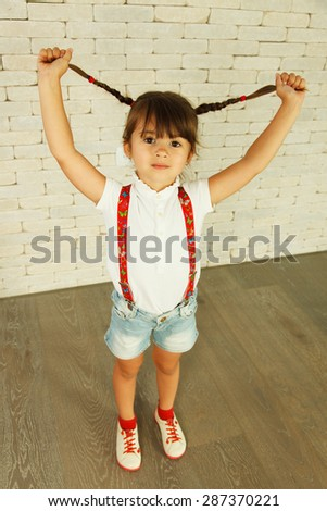Preschooler girl playing with pigtails - stock photo