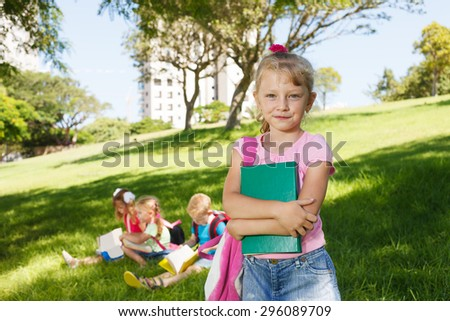 Preschooler girl with book and her friends - stock photo