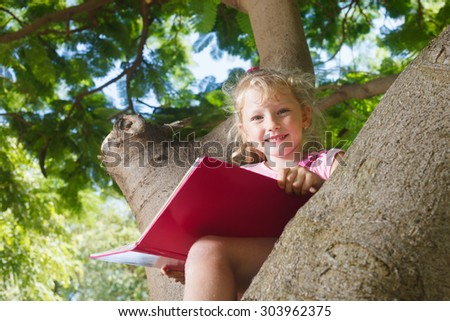 Preschooler girl with book sitting on the tree - stock photo