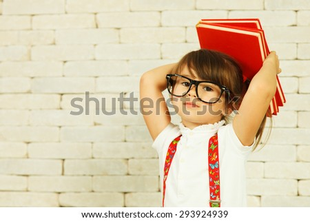 Preschooler girl with books on the head - stock photo