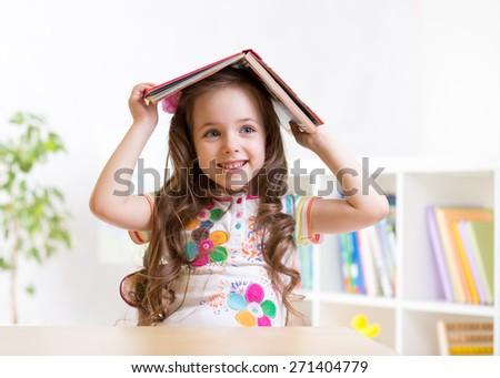preschooler kid girl with book over her head indoors - stock photo