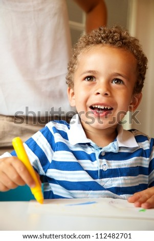Preschooler looking happy and having fun while doing a coloring activity in class - stock photo