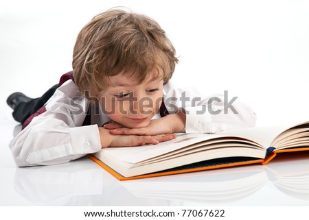 Preschooler reading book while lying on the floor - stock photo