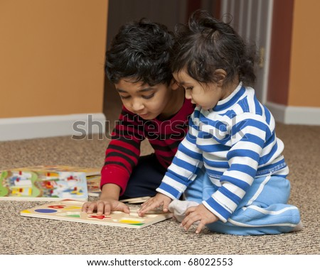 Preschooler showing Baby Sister Number and Shapes Puzzle - stock photo