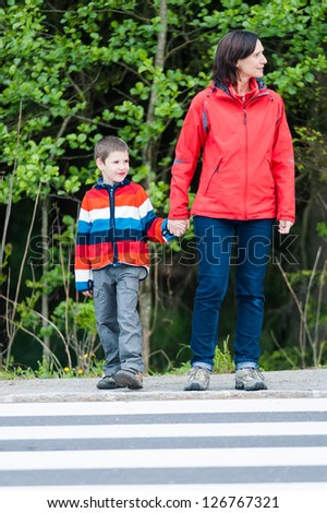 Preschooler with Mother by the Crosswalk, waiting to cross the road - stock photo