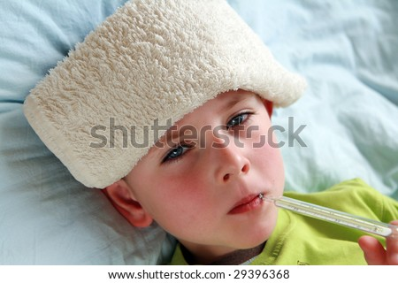 Preschooler with thermometer and compress lying in bed with flu and fever. - stock photo
