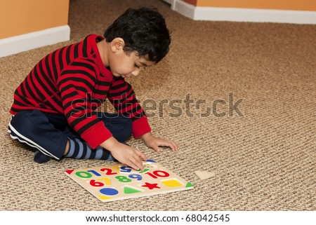 Preschooler Working On Numbers and Shapes Puzzle - stock photo