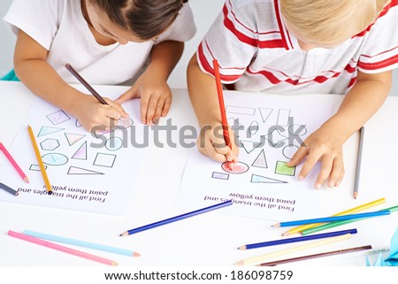 Preschoolers coloring different figures in classroom - stock photo