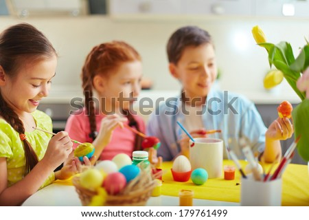 Preschoolers decorating Easter eggs, focus on happy little girl - stock photo