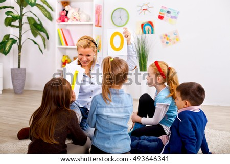 Preschoolers looking at teacher while she shows them letters