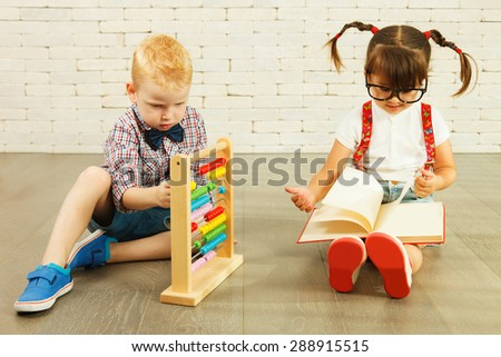 Preschoolers with abacus and book - stock photo