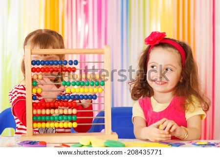Preschoolers working together with Colorful Abacus Beads - stock photo