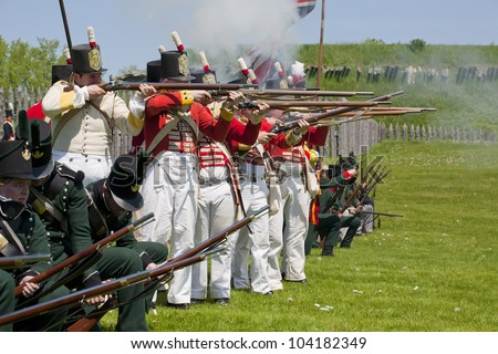 PRESCOTT, ONTARIO - MAY 21: British soldiers and Colonial regiment group firing their flintlock rifles during a reenactment of the War of 1812, on May 21, 2012 at Fort Wellington, Prescott, Ontario. - stock photo