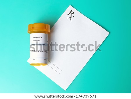 Prescription bottle and prescription on aqua background. - stock photo