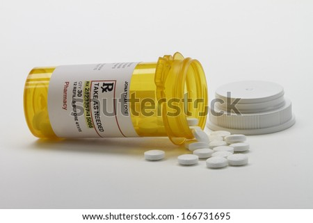 Prescription bottle on its side with pills, horizontal - stock photo