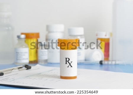 Prescription bottle on patient chart with medication bottles and supplies in background. - stock photo