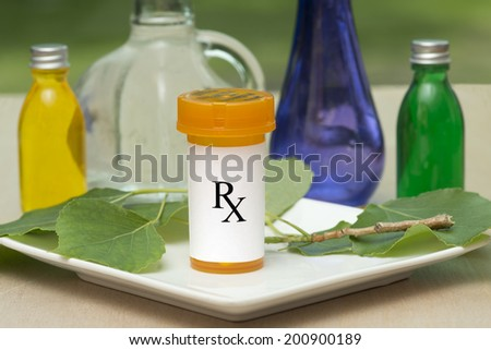 Prescription bottle with oil bottles and green leaves. - stock photo